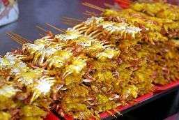 Small dried crab kebabs are piled up on trays.