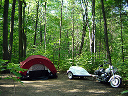 A rustic camp site in a forest with a tent, a motorcycle and a trailer.