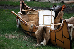 Ancestral canoe on the ground and loaded with fur and trapper equipment.