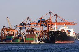A panoramic view of port activities: containers, cranes, and a moored boat.