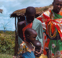 Two African adults and two young African children wearing colorful clothes are posing near a hut without looking at the camera.