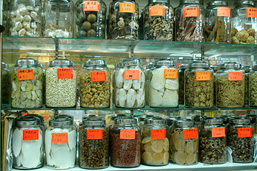 Display of various organic products, placed in labeled glass jars and aligned in three rows.