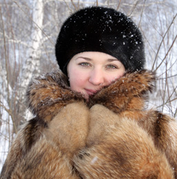 A woman wearing a fur coat and a hat looks at the camera.