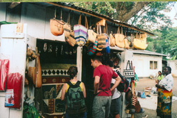 Three tourists look at a local artcraft outdoor stand.