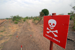 The entrance of a no man's land and a red sign with a death note on which is written: Danger, land mines.
