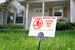 Small sign standing on a lawn informing of the spraying of pesticides.