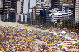 Aerial view of a beach crowded with tourists and mulitcoloured umbrellas with buildings in the background.