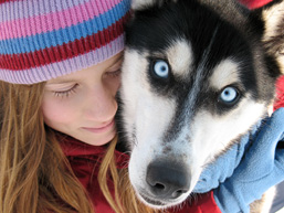 Close-up of a young girl embracing the head of a dog staring at the camera.