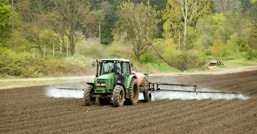 A tractor in action in a plowed field spraying chemical products.