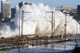 A gigantic wave dramatically hits the coastline of an industrialized city.