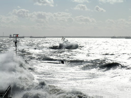 A panoramic view of a wild sea with waves submerging a pontoon.