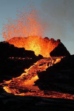 The peak of an erupting volcano with a lava flow cascading down its side.